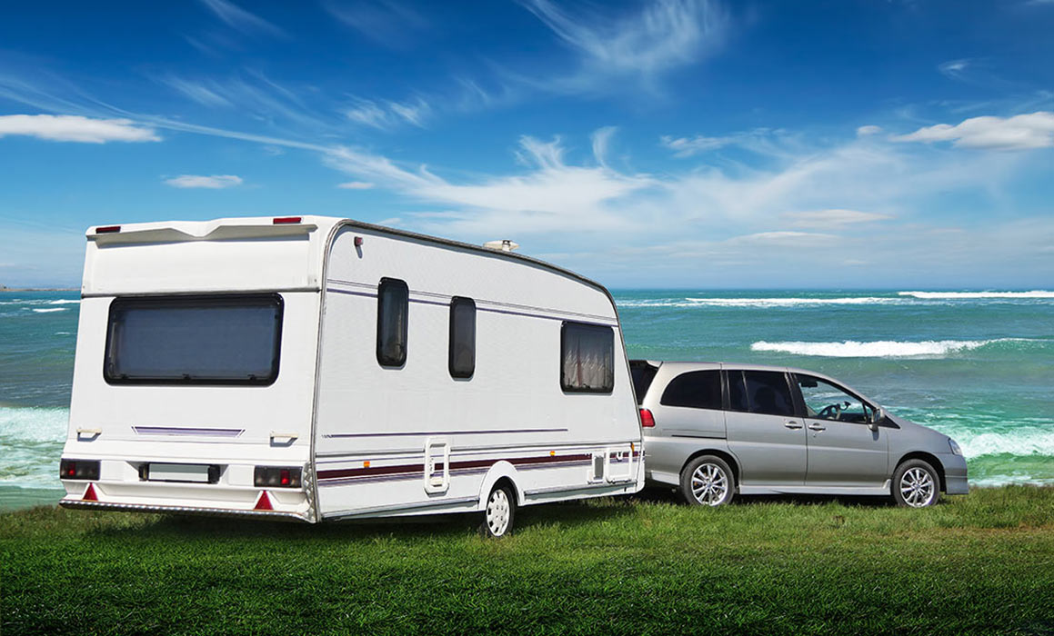 Car towing touring caravan by seaside