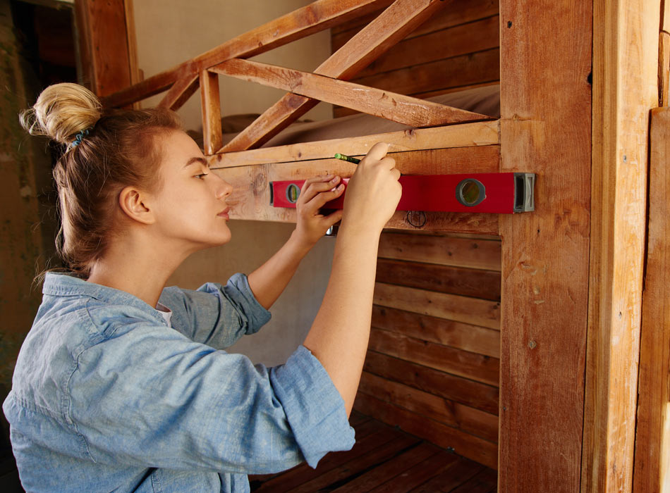 Woman measuring timber frame for self buid project
