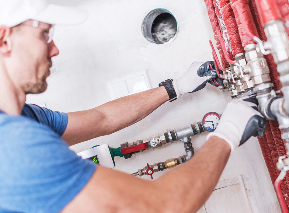 Plumber checking pressure in pipes
